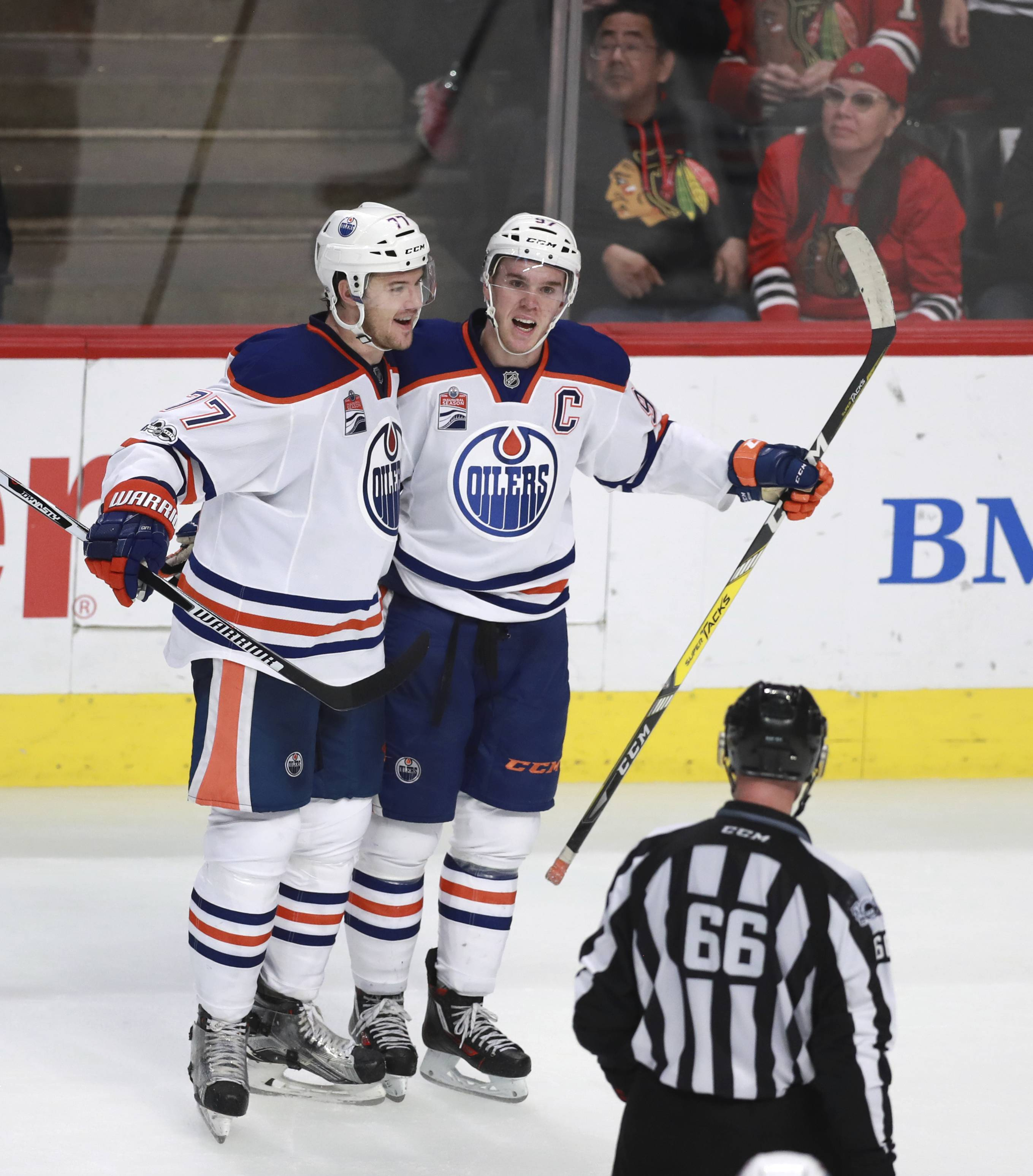 Edmonton Oilers center Connor McDavid (97) celebrates his empty net goal against the Chicago Blackhawks with teammate Oscar Klefbom (77) during the third period of an NHL hockey game Saturday, Feb. 18, 2017, in Chicago. (AP Photo/Jeff Haynes)