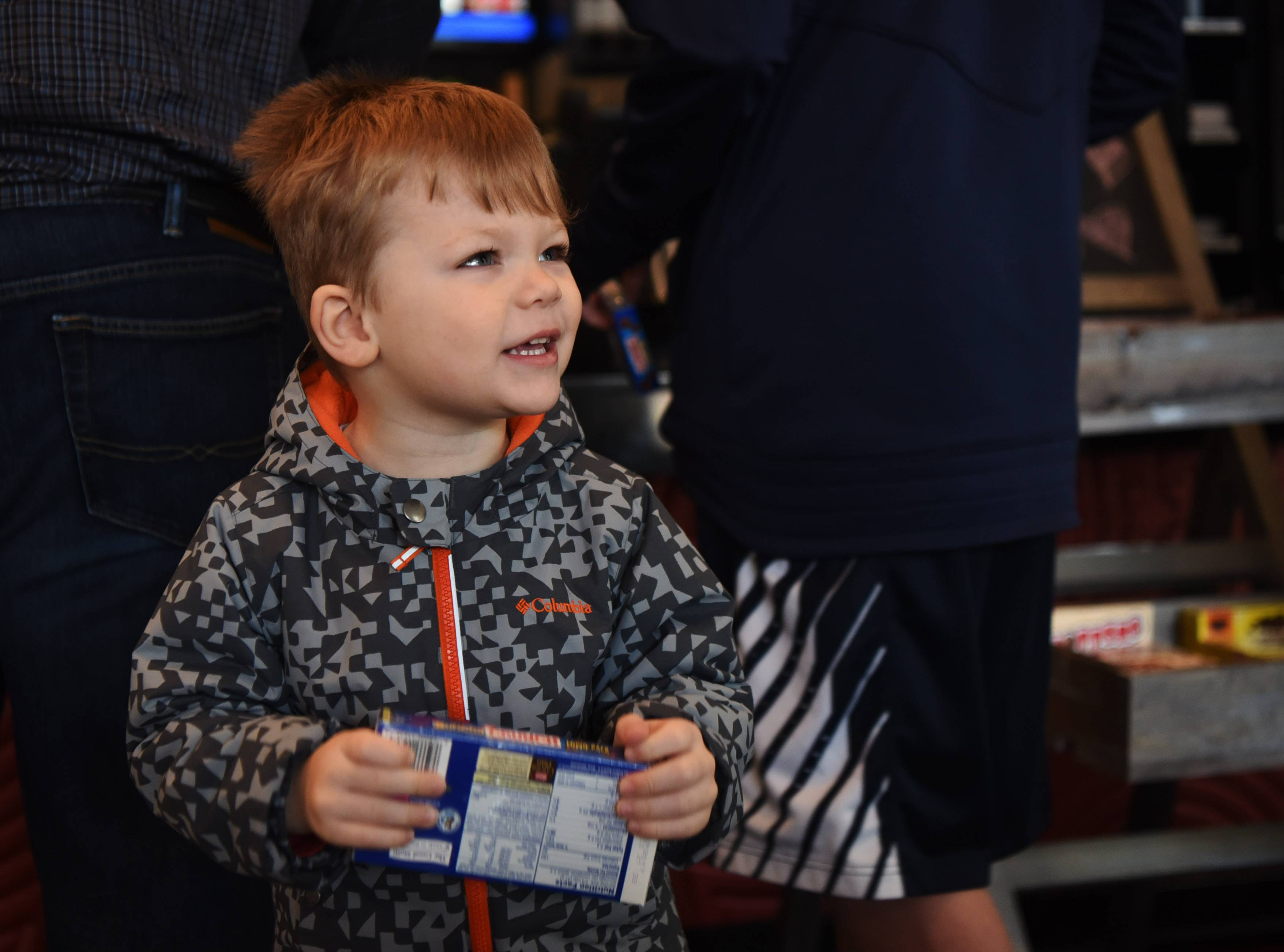 Jacob Lichner, 3, of Arlington Heights, holds his candy selection at the concession stand while attending a sensory-friendly movie with his dad, Kirk, and brother, A.J., at the Paragon Theater in Arlington Heights.
