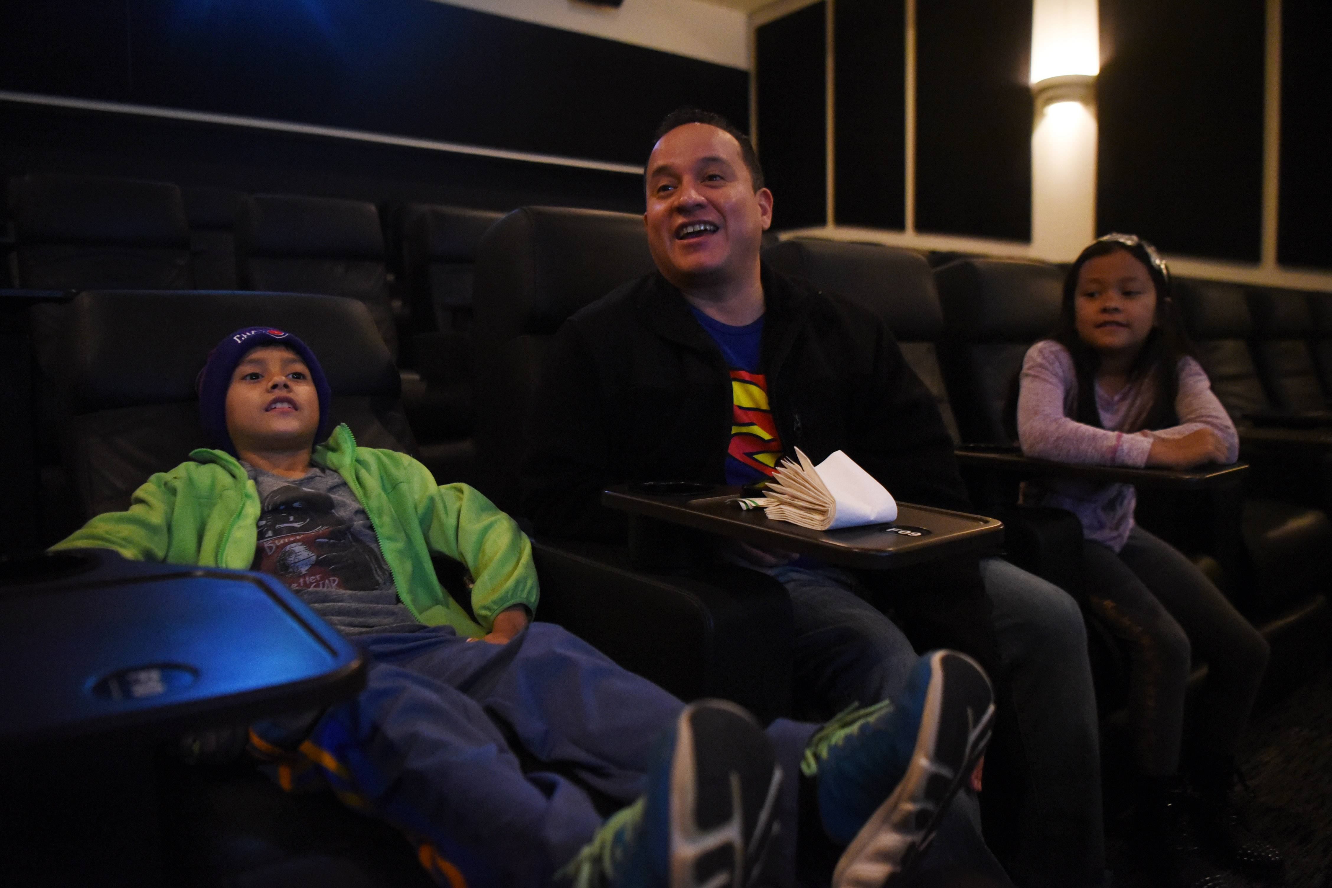 "Paul Litardo and his children, Xavier, 9, and Mia, 7, attend a sensory-friendly screening of ""The Lego Batman Movie"" at the Paragon Theater in Arlington Heights."