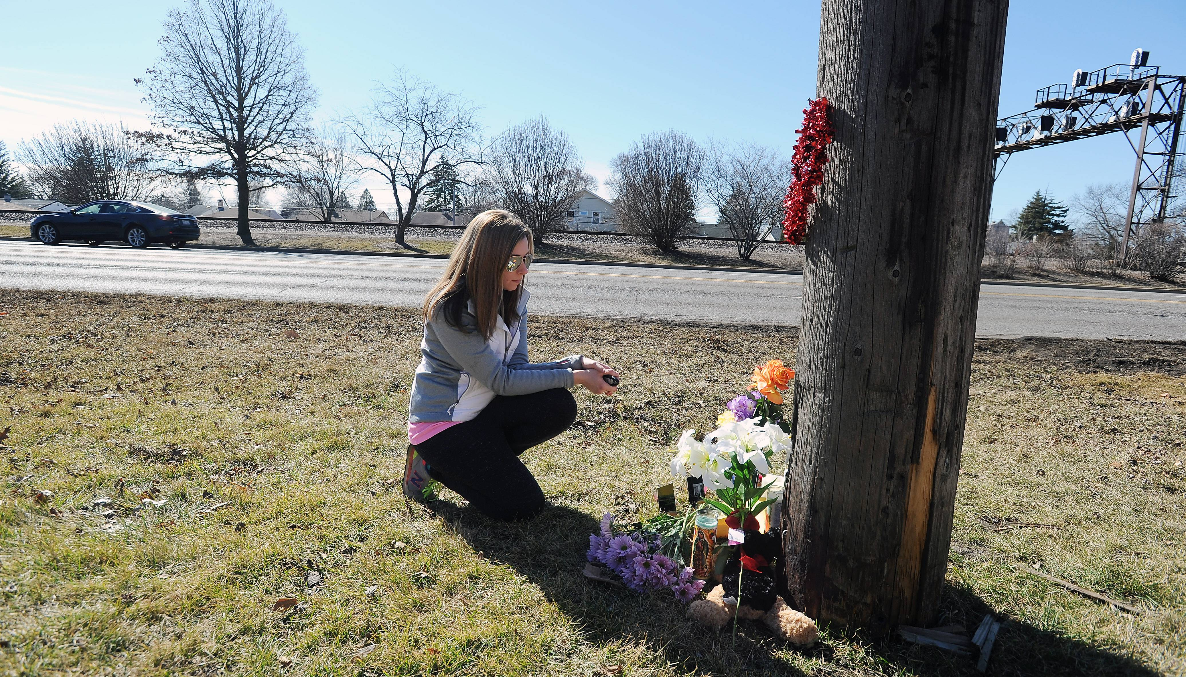 Kristen Benwitz of Mount Prospect brings a card from her son Jack and white lillies to a makeshift memorial for the Crawford family members killed in an auto crash Thursday night. The memorial is near the site of the crash along Northwest Highway in Des Plaines.