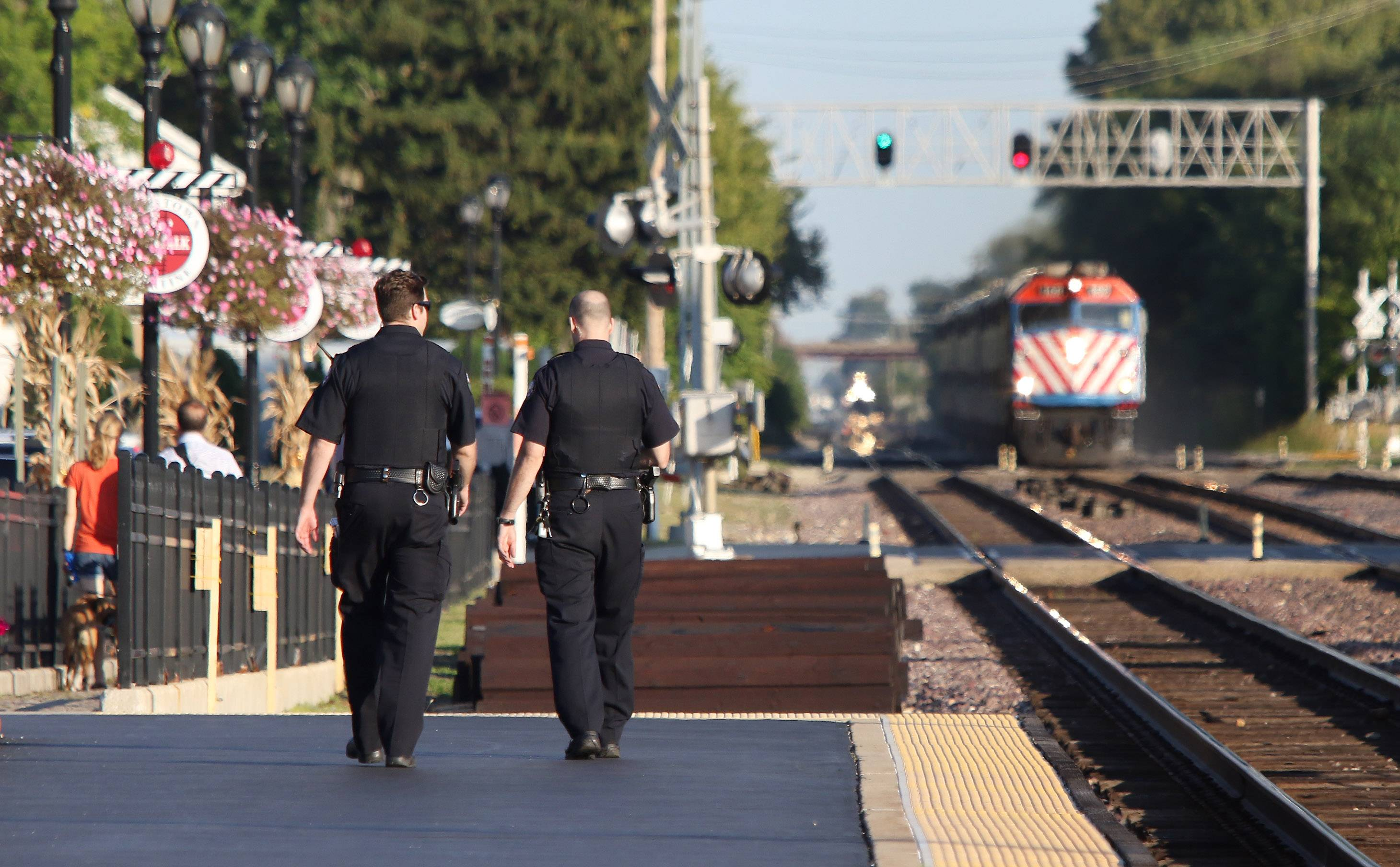 Police watch pedestrians at the Palatine Metra Station to guard against people illegally crossing over the tracks.