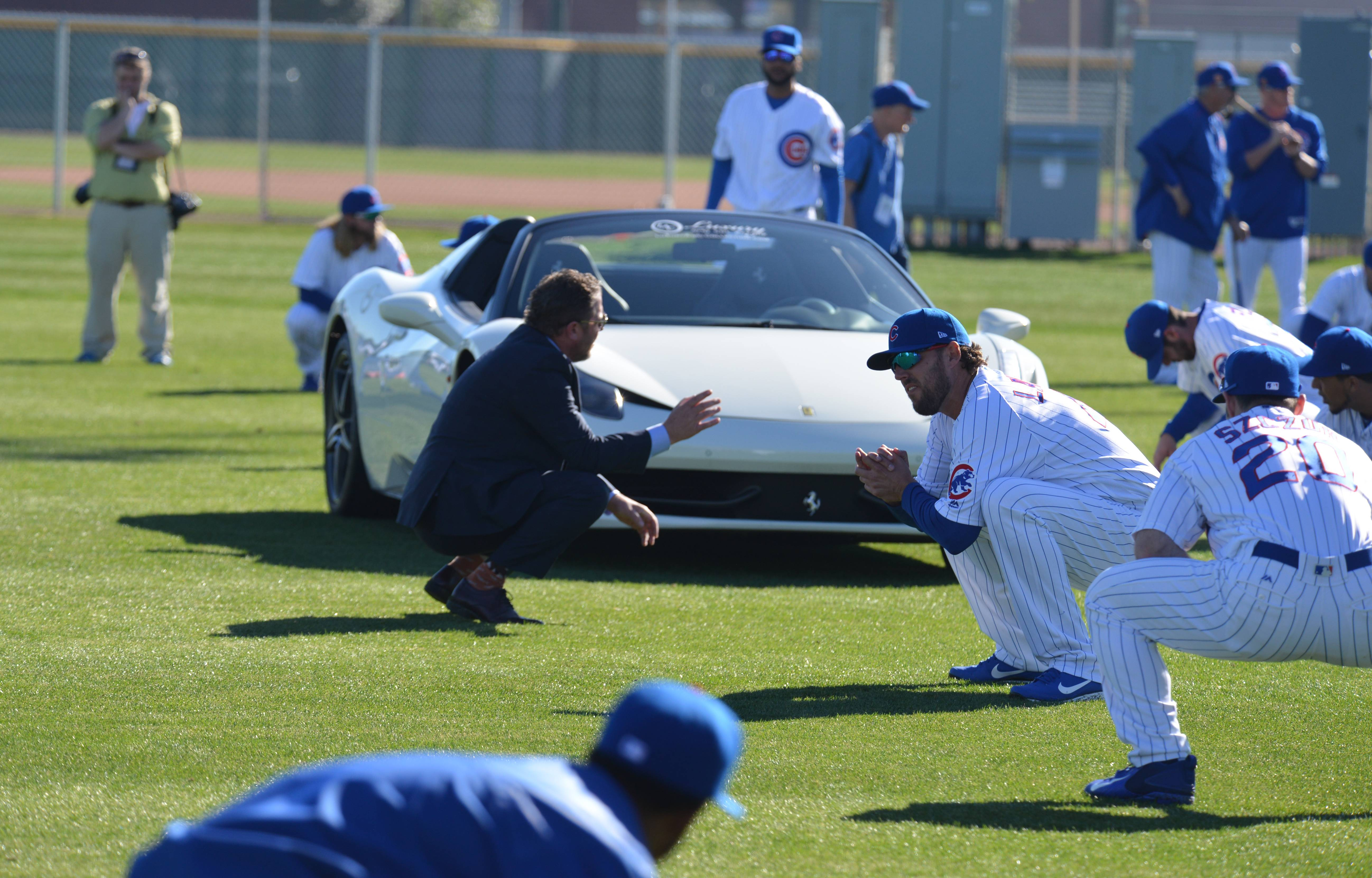 Tim Buss leads the Chicago Cubs in a workout wearing a suit that he wore while driving this Ferrari into camp.