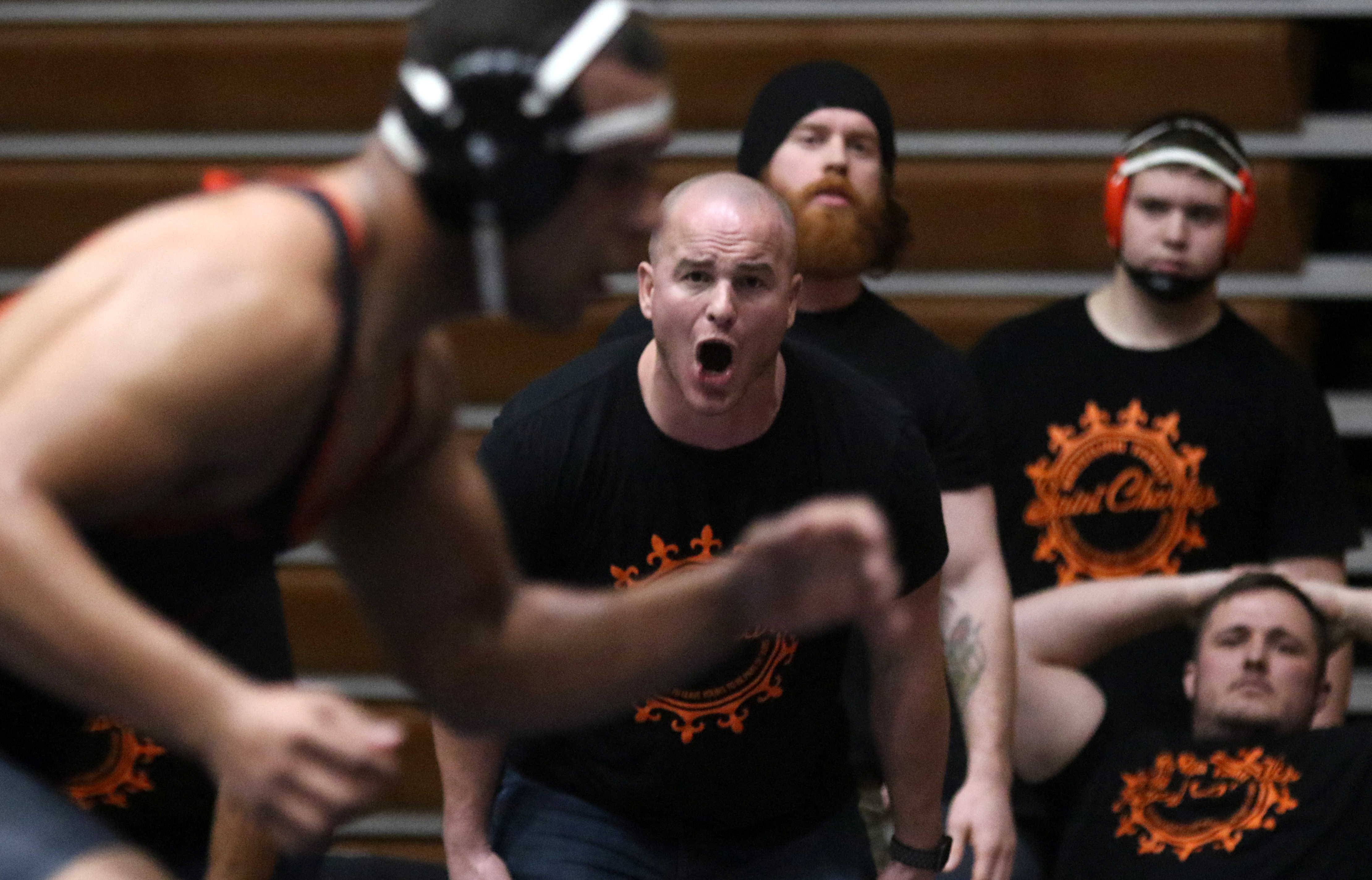 St. Charles East coach Jason Potter offers encouragement to  Darrell Gregg against Oak Park-River Forest's Elijah Osit during the 195-pound match of team wrestling sectional action at William N. Perry Gymnasium at Conant on Tuesday.