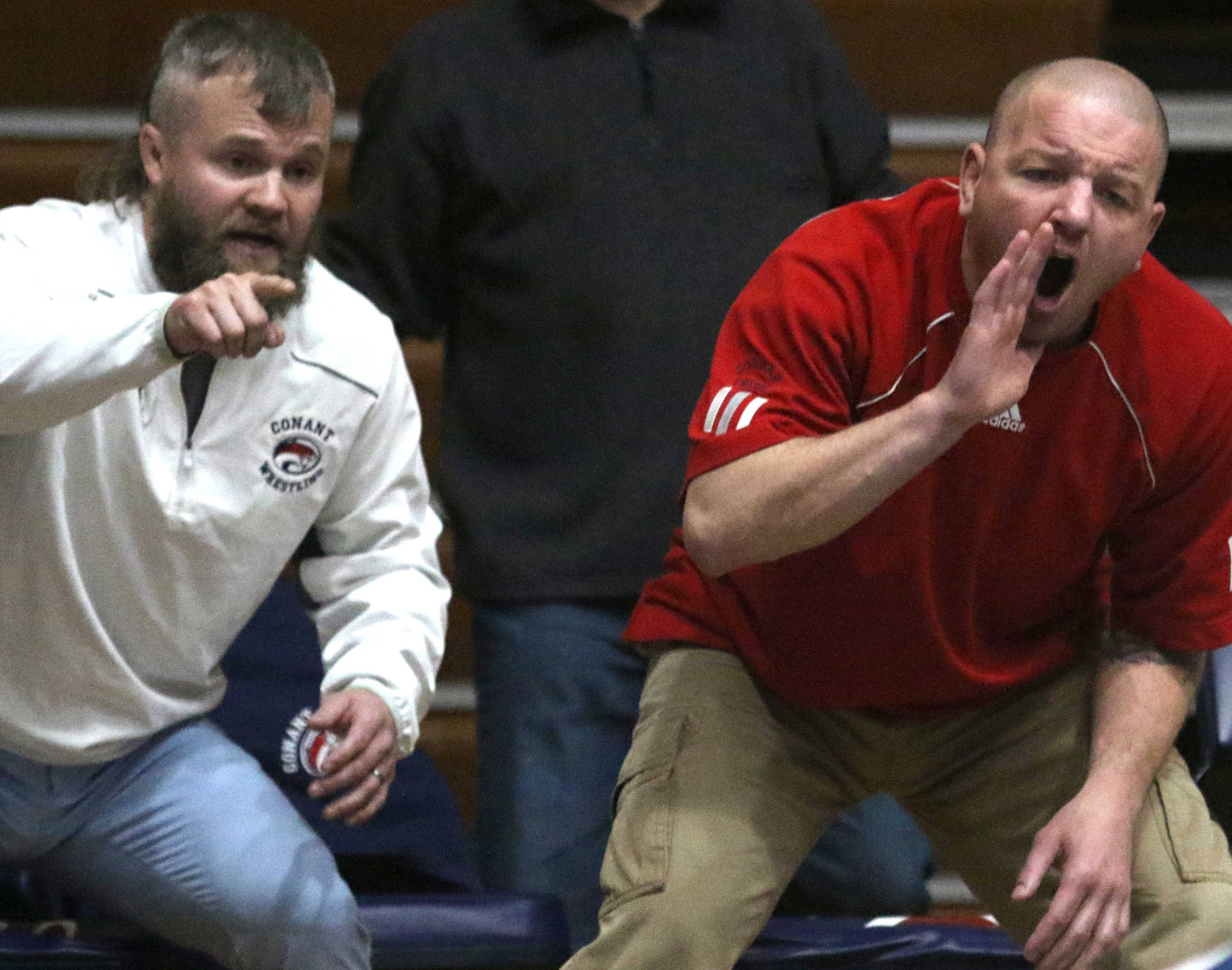 Conant coach Chad Hay, left, and assistant coach Chris Winter guide their wrestlers against Notre Dame during team wrestling sectional action at William N. Perry Gymnasium at Conant on Tuesday.