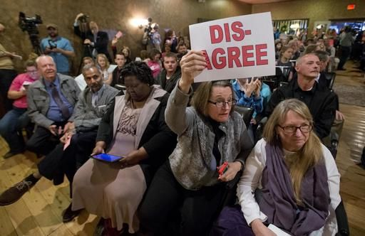 Constituents of Congressman Dave Brat, R-Va., hold signs as he answers questions during a town hall meeting with the congressman in Blackstone, Va., Tuesday, Feb. 21, 2017.