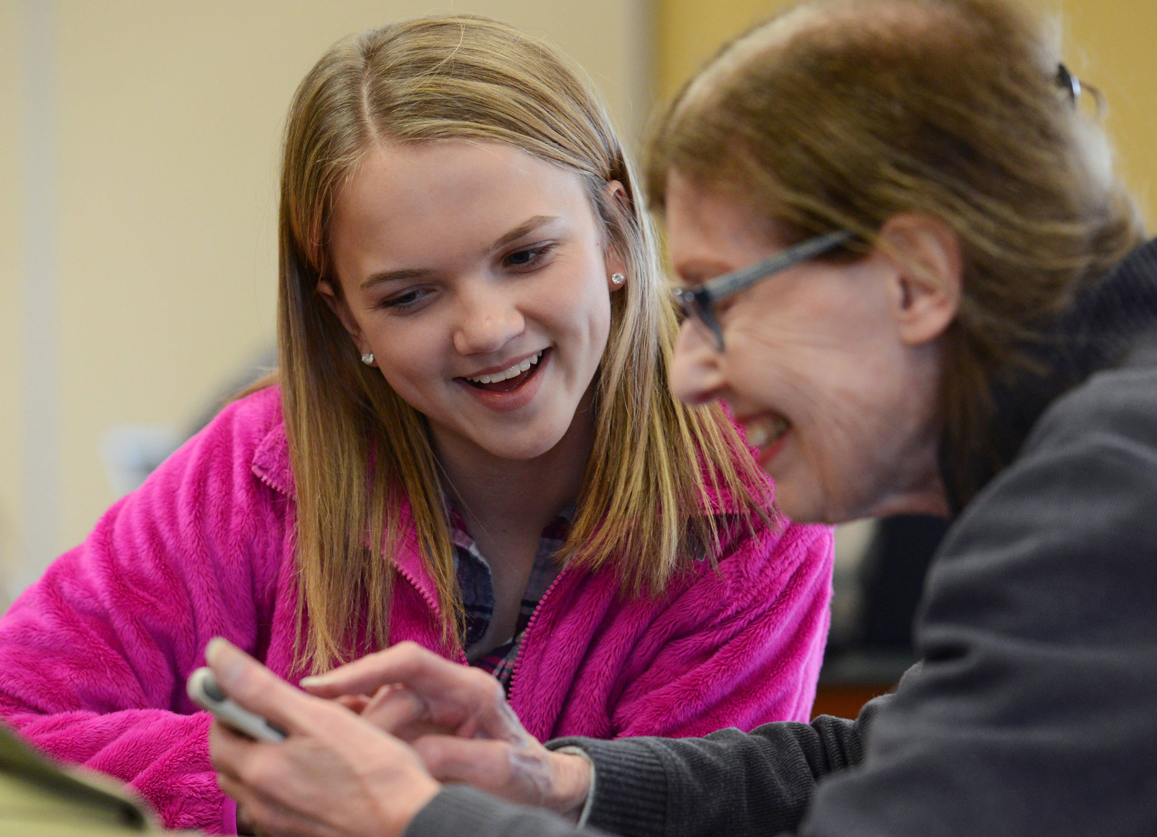 Fremont Middle School student Hope Peterson helps Sue Lewis, a resident of the Grand Dominion community in Mundelein, with her smartphone Thursday. About a dozen Fremont students visited Grand Dominion to help teach residents how best to use their phones, tablets and computers.