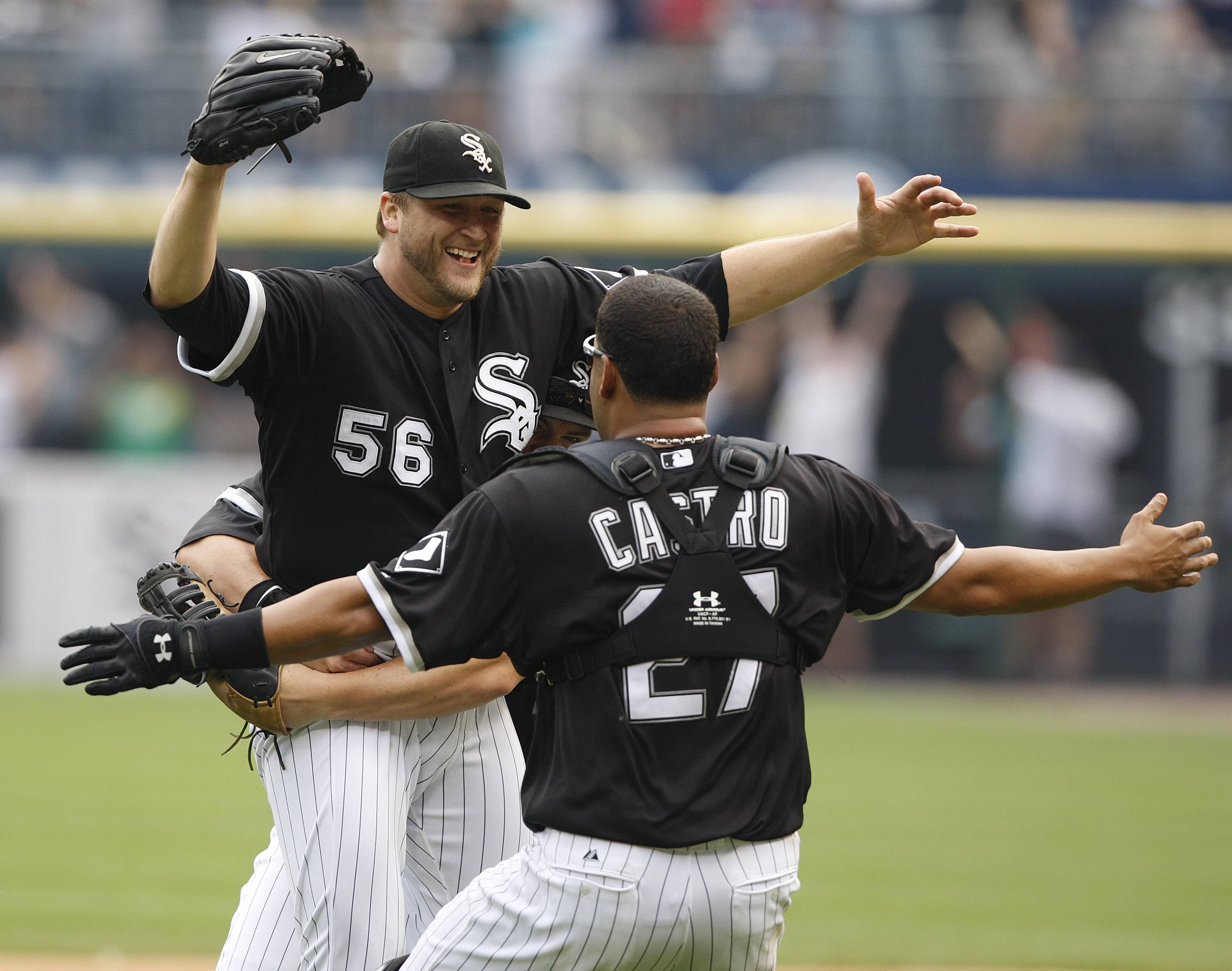 Chicago White Sox pitcher Mark Buehrle, left, is embraced by teammates including catcher Ramon Castro after throwing a perfect game against the Tampa Bay Rays in a baseball game, Thursday, July 23, 2009, in Chicago. The White Sox won 5-0. (AP Photo/Jim Prisching)