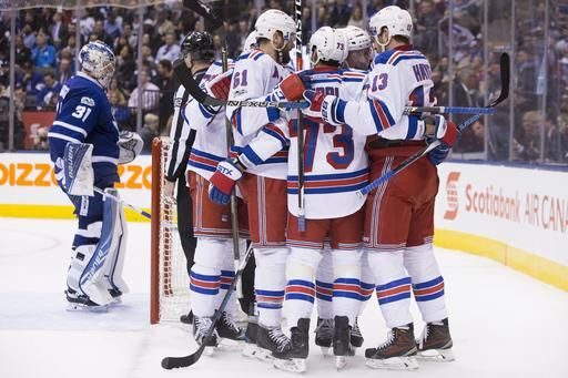 New York Rangers left wing J.T. Miller (10) gets mobbed by teammates after scoring the game-tying goal on Toronto Maple Leafs goalie Frederik Andersen (31) during the third period of an NHL hockey game in Toronto on Thursday, Feb. 23, 2017. New York won, 2-1, in shootout. (Chris Young/The Canadian Press via AP)