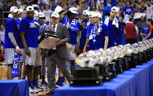 Kansas coach Bill Self carries his 13th Big 12 championship trophy following the team's NCAA college basketball game against TCU in Lawrence, Kan., Wednesday, Feb. 22, 2017. Kansas defeated TCU 87-68. (AP Photo/Orlin Wagner)
