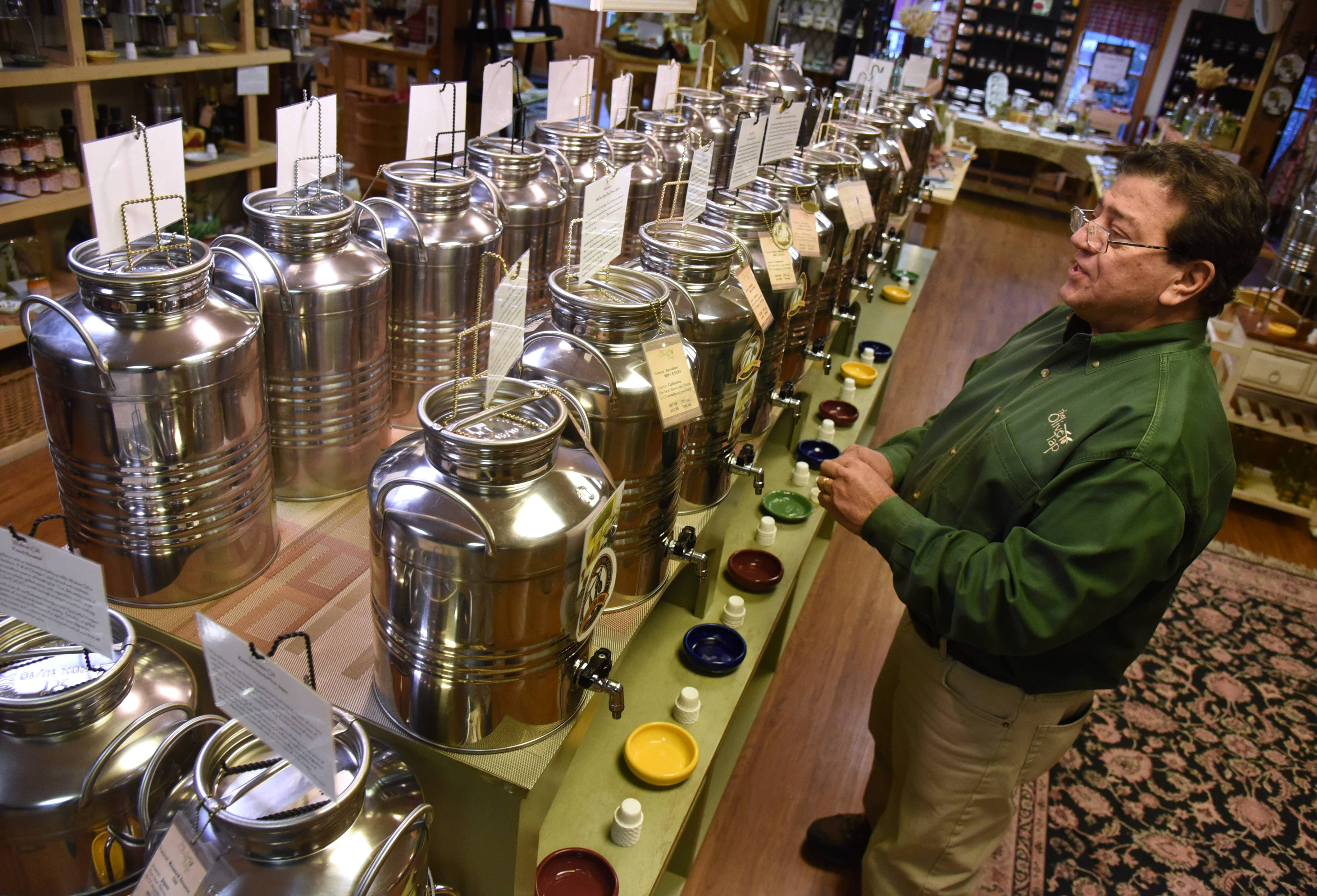 The Olive Tap owner Rick Petrocelly looks over tanks of oil in his Long Grove store. He said the olive shortage in Europe could lead to some modest price increases.