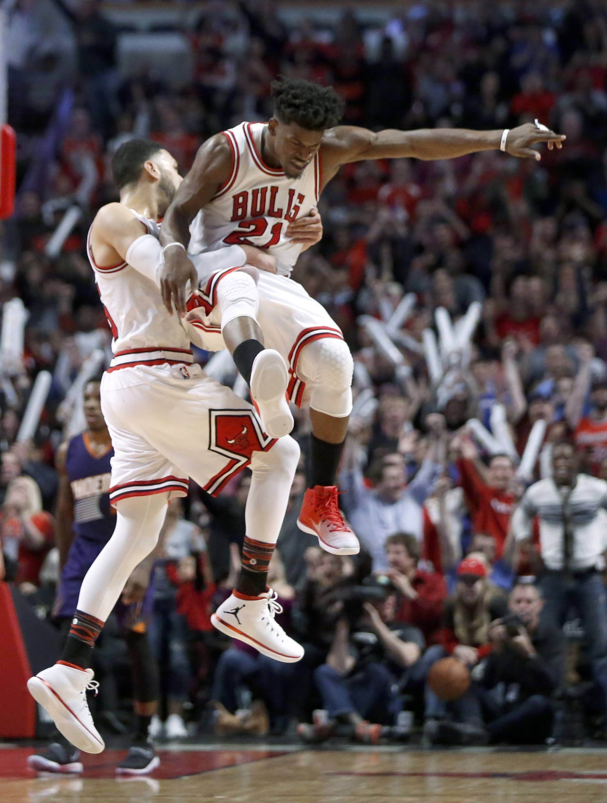 Chicago Bulls' Jimmy Butler (21) celebrates his game-tying shot with Denzel Valentine, late in the second half of the team's NBA basketball game against the Phoenix Suns on Friday, Feb. 24, 2017, in Chicago. The Bulls won in overtime, 128-121. (AP Photo/Charles Rex Arbogast)