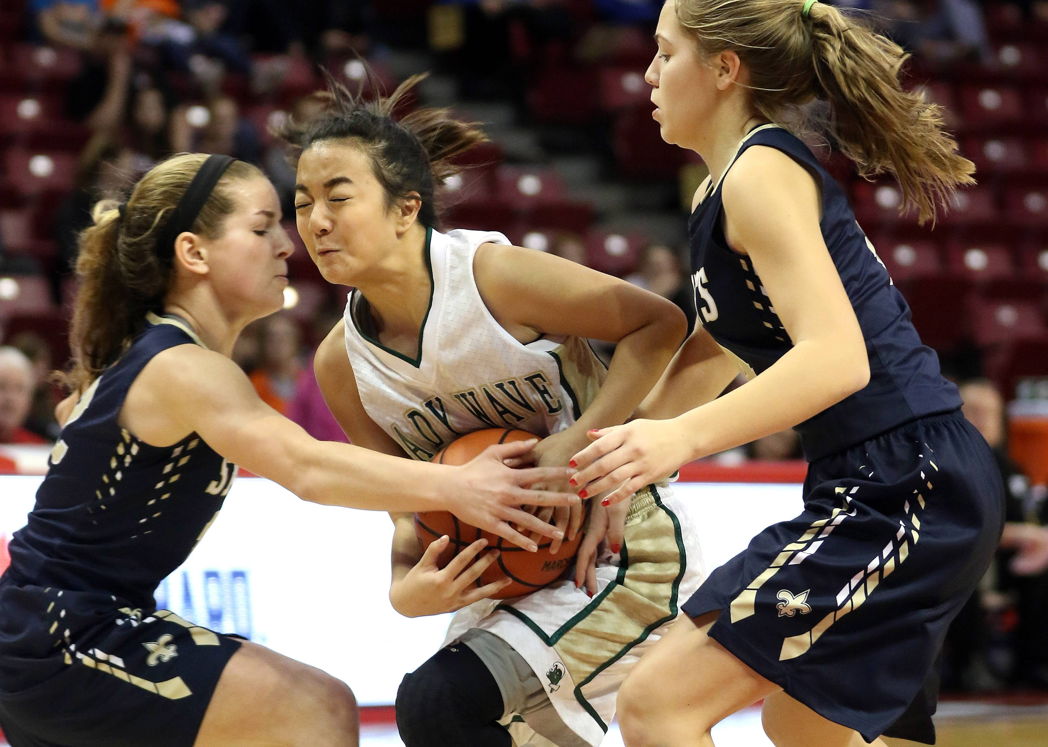 St. Edward's Yssa Sto. Domingo, middle, drives through Central Catholic's Lauren Shanks and Charlie Sartoris.