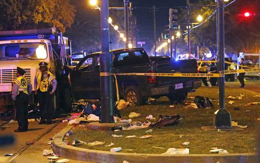 Police stand next to a pickup truck that slammed into a crowd and other vehicles, causing multiple injuries, coming to a stop against a dump truck, during the Krewe of Endymion parade in New Orleans, Saturday, Feb. 25, 2017. (AP Photo/Gerald Herbert)