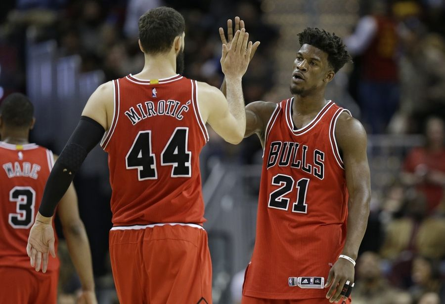 Chicago Bulls' Nikola Mirotic (44) and Jimmy Butler (21) celebrate late in the second half of an NBA basketball game against the Cleveland Cavaliers, Saturday, Feb. 25, 2017, in Cleveland.