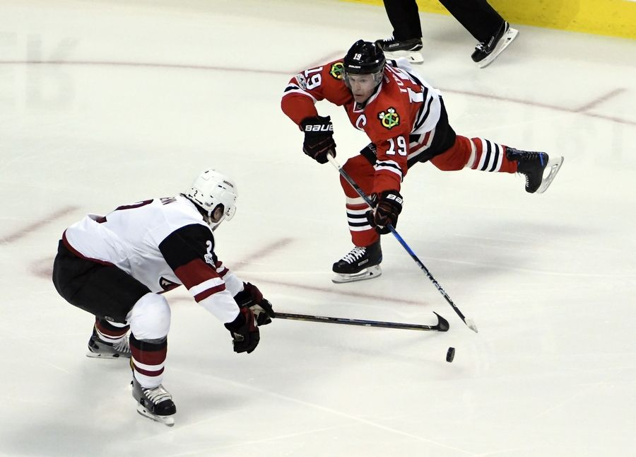 Blackhawks center Jonathan Toews passes the puck around Arizona Coyotes defenseman Luke Schenn Thursday in Chicago.