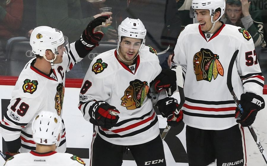 Chicago Blackhawks' Nick Schmaltz, center, is congratulated by Jonathan Toews, left, after his goal off Minnesota Wild goalie Devan Dubnyk during the third period of an NHL hockey game Tuesday, Feb. 21, 2017, in St. Paul, Minn. The Blackhawks won 5-3. Toews scored three goals in the game.