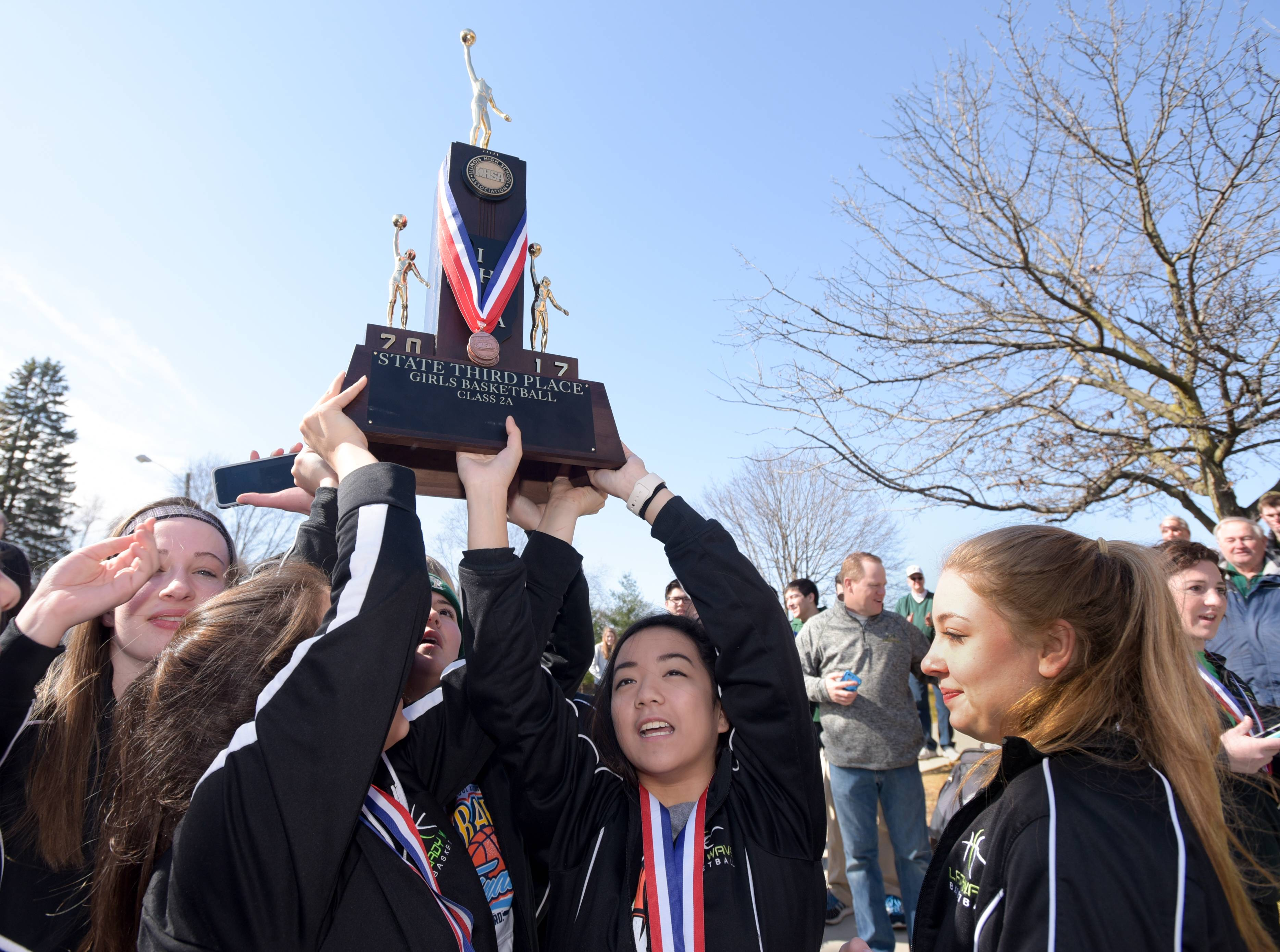 Members of the St. Edward high School girls basketball team returned to the school's Elgin campus Sunday with their trophy for finishing third in the Class 2A state tournament over the weekend.