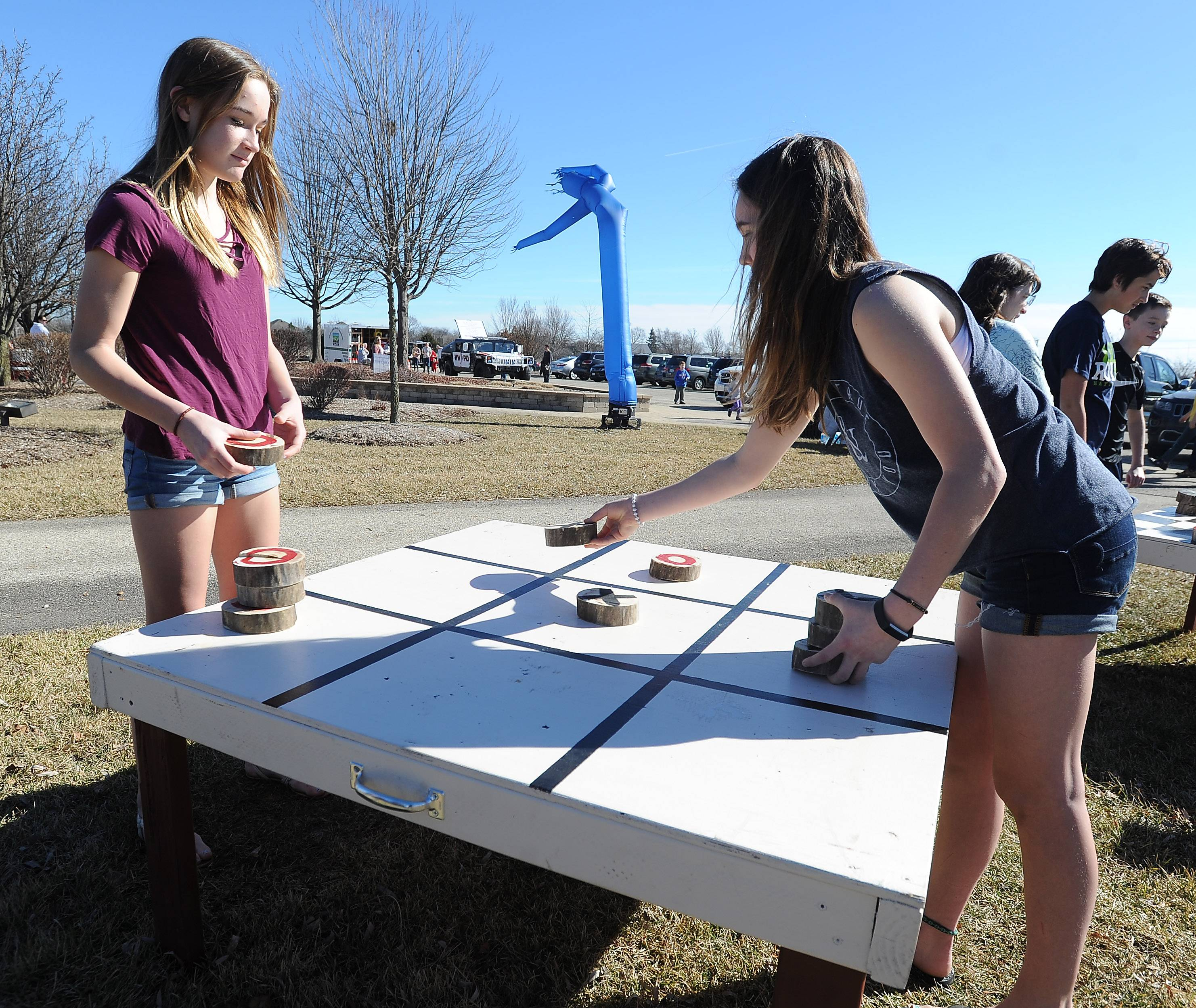 Taylor Meents, 15, and her sister Samantha, 14, of Hawthorn Woods play tick-tac-toe in their shorts in very spring-like conditions on Saturday at the Hawthorn Woods Winter Carnival.