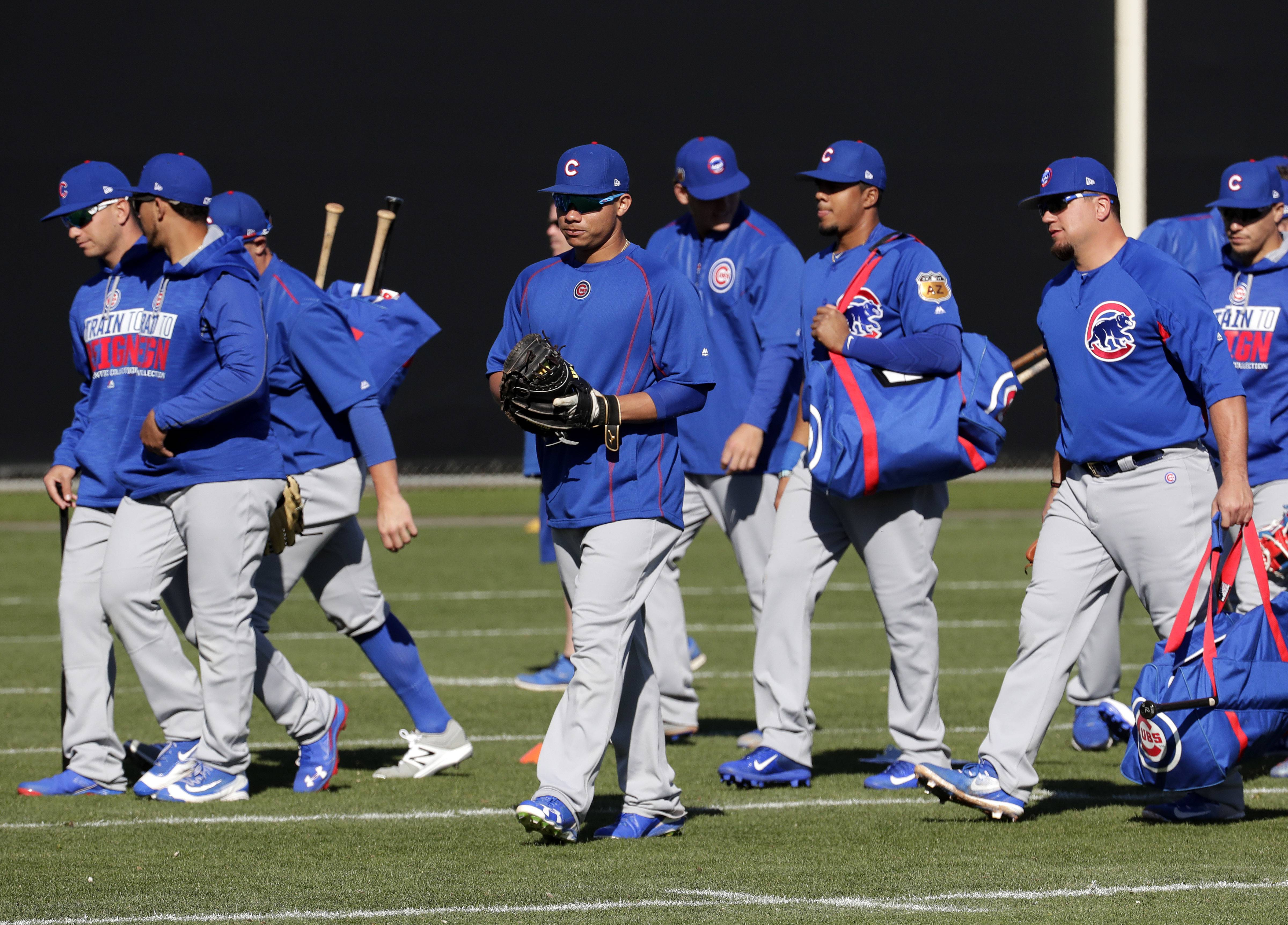 Chicago Cubs players arrive for workouts during a spring training baseball practice, Friday, Feb. 24, 2017, in Mesa, Ariz. (AP Photo/Matt York)
