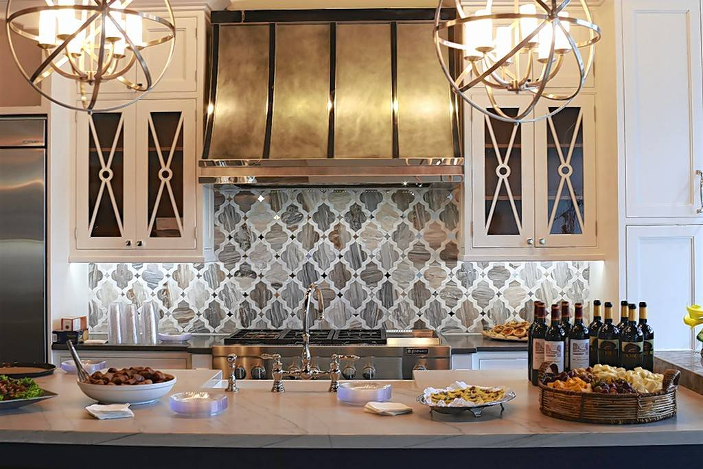 The showroom of Vineyard Chic, based in St. Charles with a showroom in Geneva, displays a kitchen with a marble backsplash and a custom metal hood. Lighting comes from a pair of metal-wrapped chandeliers.