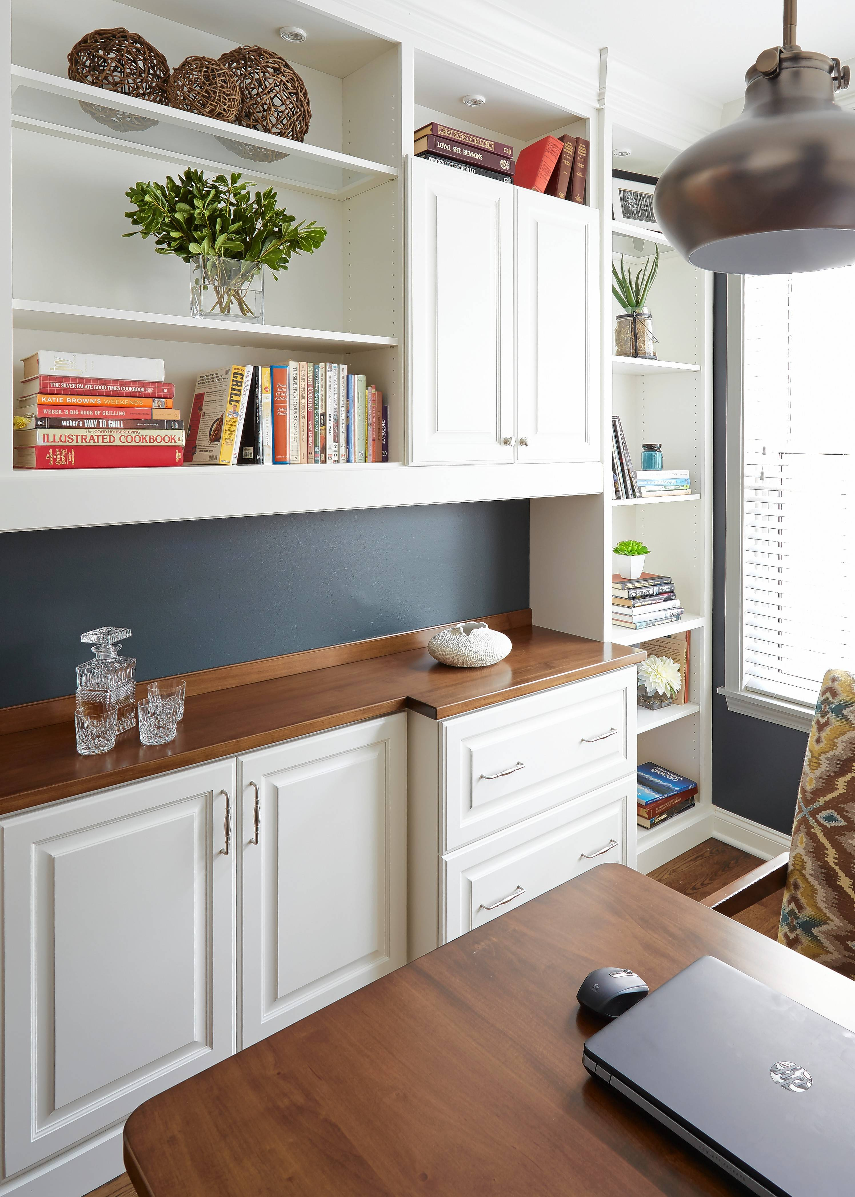 In this home office design by Jennifer McGinnis of Redux Interior Design in Lake Zurich, custom built-in cabinetry provides plenty of storage space and still show clean lines with cables and docking stations hidden.