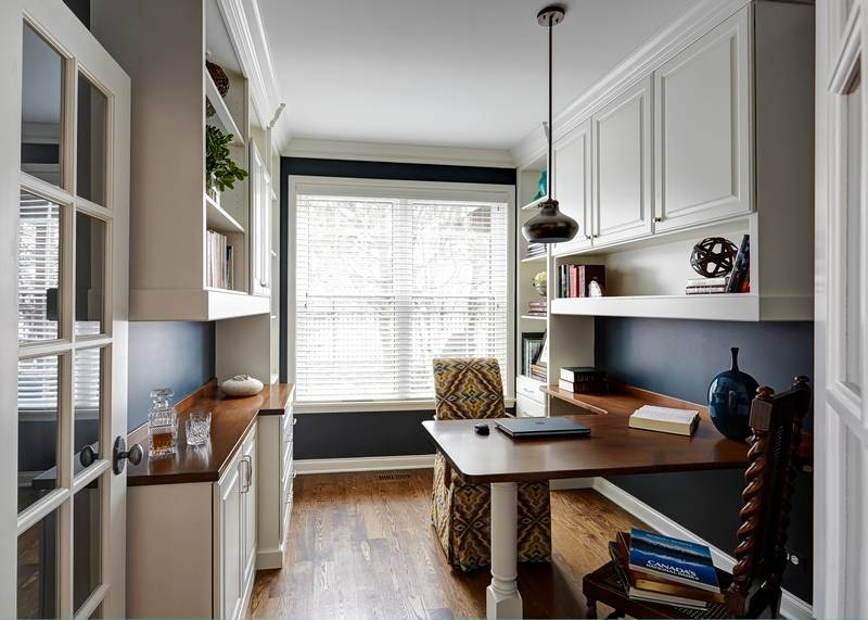 Lots of natural light helps this home office designed by Redux Interior  Design maintain an open