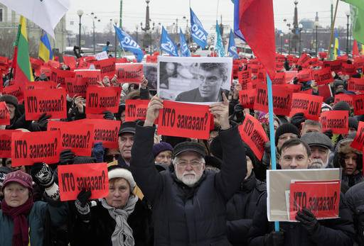 People hold posters reading 'Who ordered the murder?' during a rally in memory of opposition leader Boris Nemtsov in St. Petersburg, Russia, Sunday, Feb. 26, 2017. Thousands of Russians have taken to the streets of Moscow and St. Petersburg to mark two years since Nemtsov was gunned down outside the Kremlin.