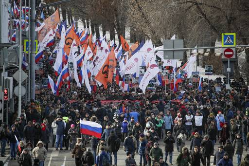 People, with flags of different opposition movements, march in memory of opposition leader Boris Nemtsov, in Moscow, Russia, Sunday, Feb. 26, 2017. Thousands of Russians take to the streets of downtown Moscow to mark two years since Nemtsov was gunned down outside the Kremlin.