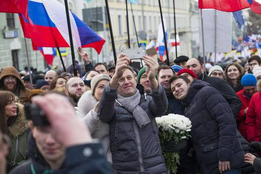 Russian opposition leader Alexei Navalny, center and his wife Yulia take a selfie during a march in memory of opposition leader Boris Nemtsov in Moscow, Russia, Sunday, Feb. 26, 2017. Thousands of Russians take to the streets of downtown Moscow to mark two years since Nemtsov was gunned down outside the Kremlin.