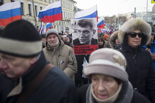 People march in memory of opposition leader Boris Nemtsov, portrait in center, in Moscow, Russia, Sunday, Feb. 26, 2017. Thousands of Russians take to the streets of downtown Moscow to mark two years since Nemtsov was gunned down outside the Kremlin. The poser reads: He died for the future.