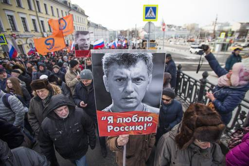 People march in memory of opposition leader Boris Nemtsov, portrait in center, in Moscow, Russia, Sunday, Feb. 26, 2017. Thousands of Russians take to the streets of downtown Moscow to mark two years since Nemtsov was gunned down outside the Kremlin. The poster reads: I love Russia.