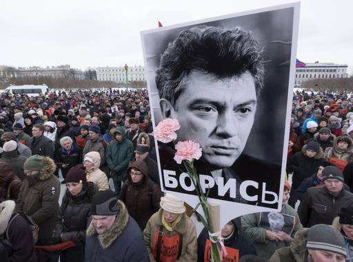 People gather in memory of opposition leader Boris Nemtsov, portrait in center, in St. Petersburg, Russia, Sunday, Feb. 26, 2017. Russians have taken to the streets of downtown Moscow and St. Petersburg to mark two years since Nemtsov was gunned down outside the Kremlin.
