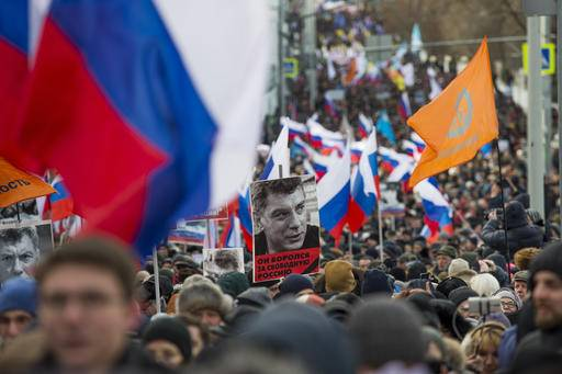 People march in memory of opposition leader Boris Nemtsov, portrait in center, in Moscow, Russia, Sunday, Feb. 26, 2017. Thousands of Russians take to the streets of downtown Moscow to mark two years since Nemtsov was gunned down outside the Kremlin.