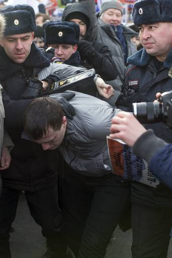 Police detain a man who threw paint in a face of former Russian Prime Minister and opposition leader Mikhail Kasyanov, during a march in memory of opposition leader Boris Nemtsov, in Moscow, Russia, Sunday, Feb. 26, 2017. Thousands of Russians take to the streets of downtown Moscow to mark two years since Nemtsov was gunned down outside the Kremlin.