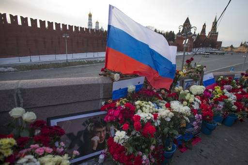 A portrait of Russian opposition leader Boris Nemtsov, a Russian national flag and flowers are laid at the place where he was gunned down, in Moscow, Russia, Sunday, Feb. 26, 2017. Thousands of Russians take to the streets of downtown Moscow to mark two years since Nemtsov was gunned down outside the Kremlin.