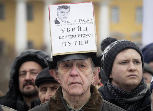 A man displays a poster reading 'Putin controls murderers' during a rally in memory of opposition leader Boris Nemtsov in St.Petersburg, Russia, Sunday, Feb. 26, 2017. Thousands of Russians have taken to the streets of downtown Moscow and St.Petersburg to mark two years since Nemtsov was gunned down outside the Kremlin.