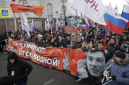 People carry a poster, reading: Heroes do not die! Russia will be free! during a march in memory of opposition leader Boris Nemtsov, in Moscow, Russia, Sunday, Feb. 26, 2017. Thousands of Russians take to the streets of downtown Moscow to mark two years since Nemtsov was gunned down outside the Kremlin.