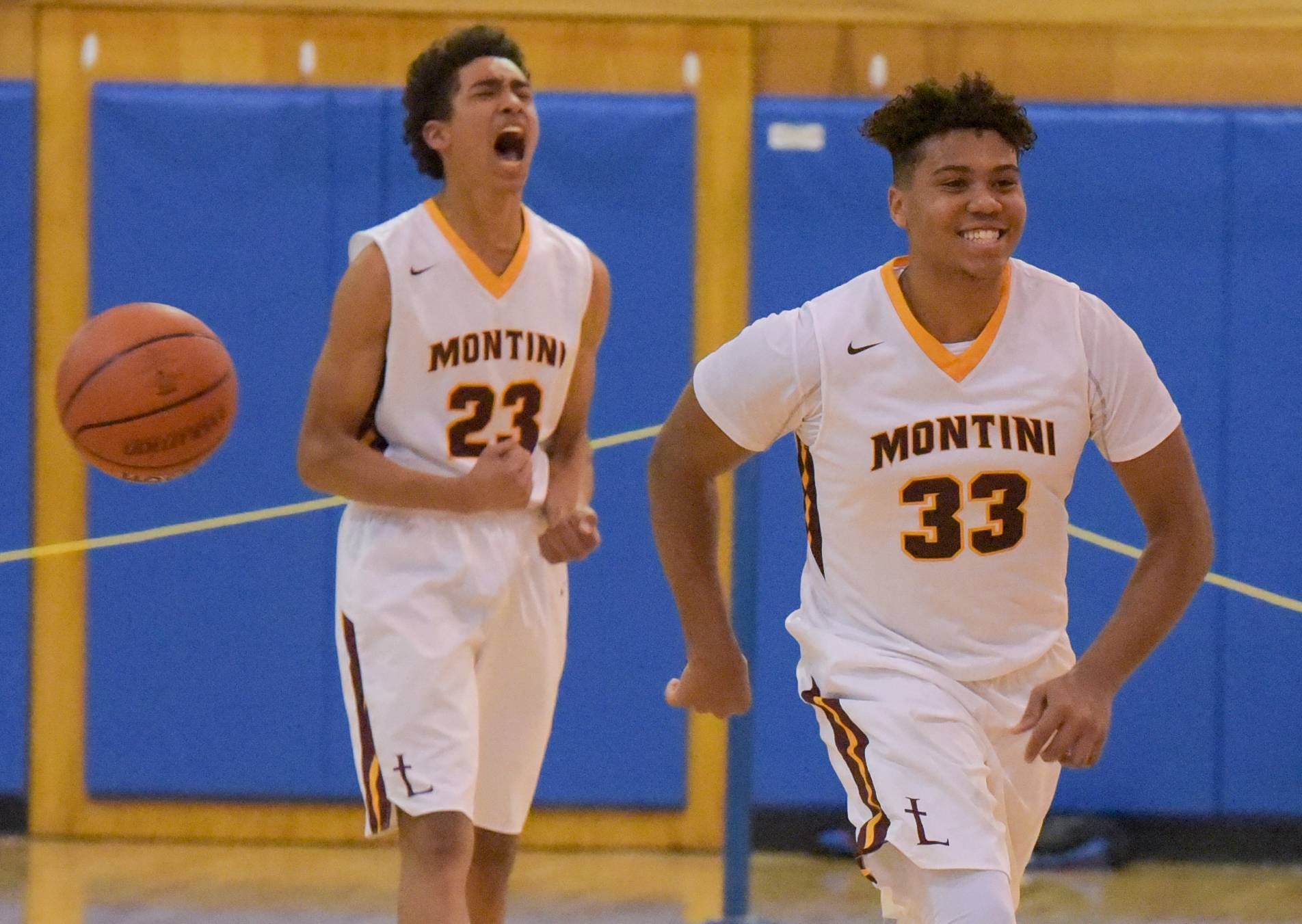 Montini's Kevin Brachmann and Jayston Williams celebrate the Broncos 87-83 win over Marmion Academy during the Class 3A regional boys basketball game Monday at Marmion Academy.