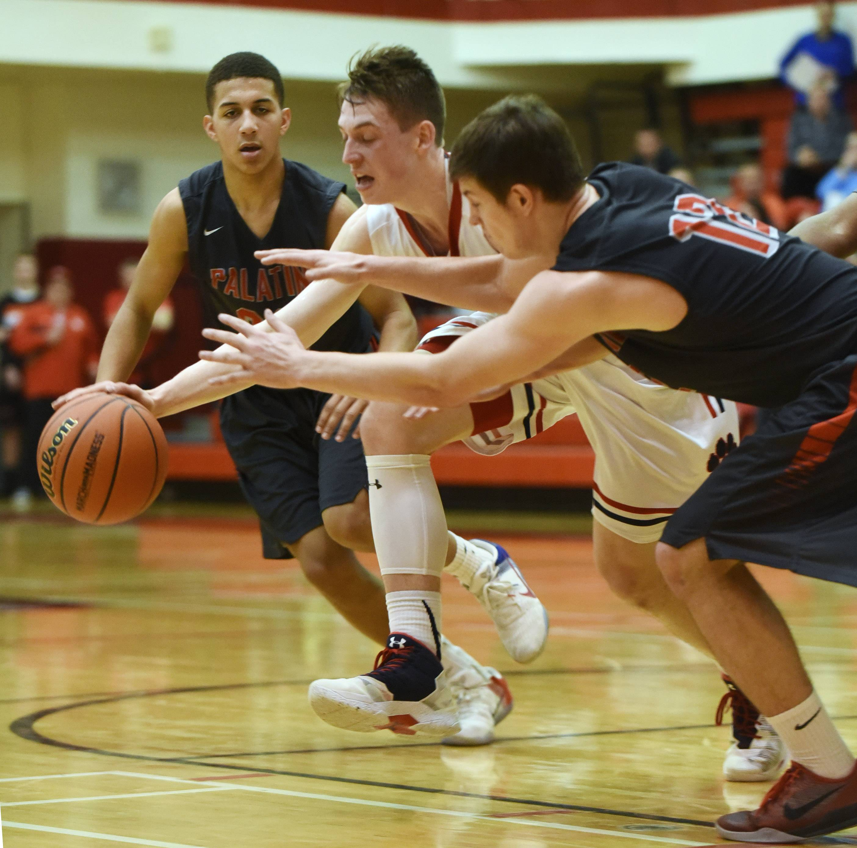 Conant's Jimmy Sotos, right, tries to maintain possession of the ball while making a move between Palatine's Lamon Berry, left, and Johnny O'Shea during the Class 4A regional semifinal at Palatine Tuesday