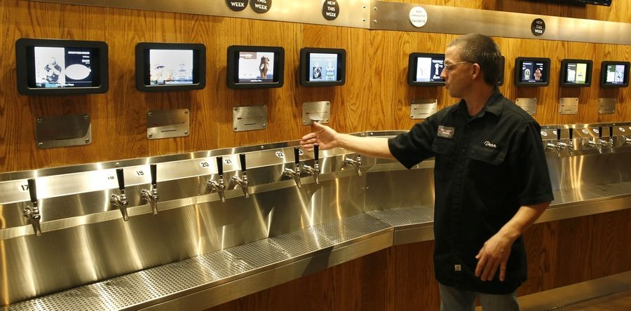 Self-serve taps are a unique beer distribution system displayed by Dean Schiada, manager at Red Arrow Tap Room in Elmhurst.
