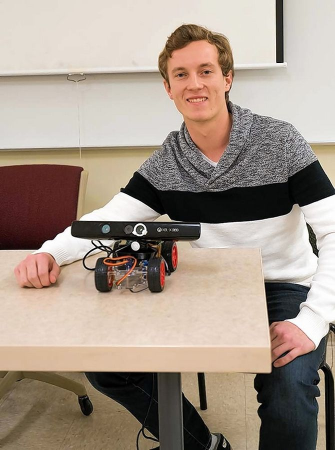 Benedictine University student Jakub Jancek with the Kinect robot he will present at a symposium for computer science education in Seattle, Washington.