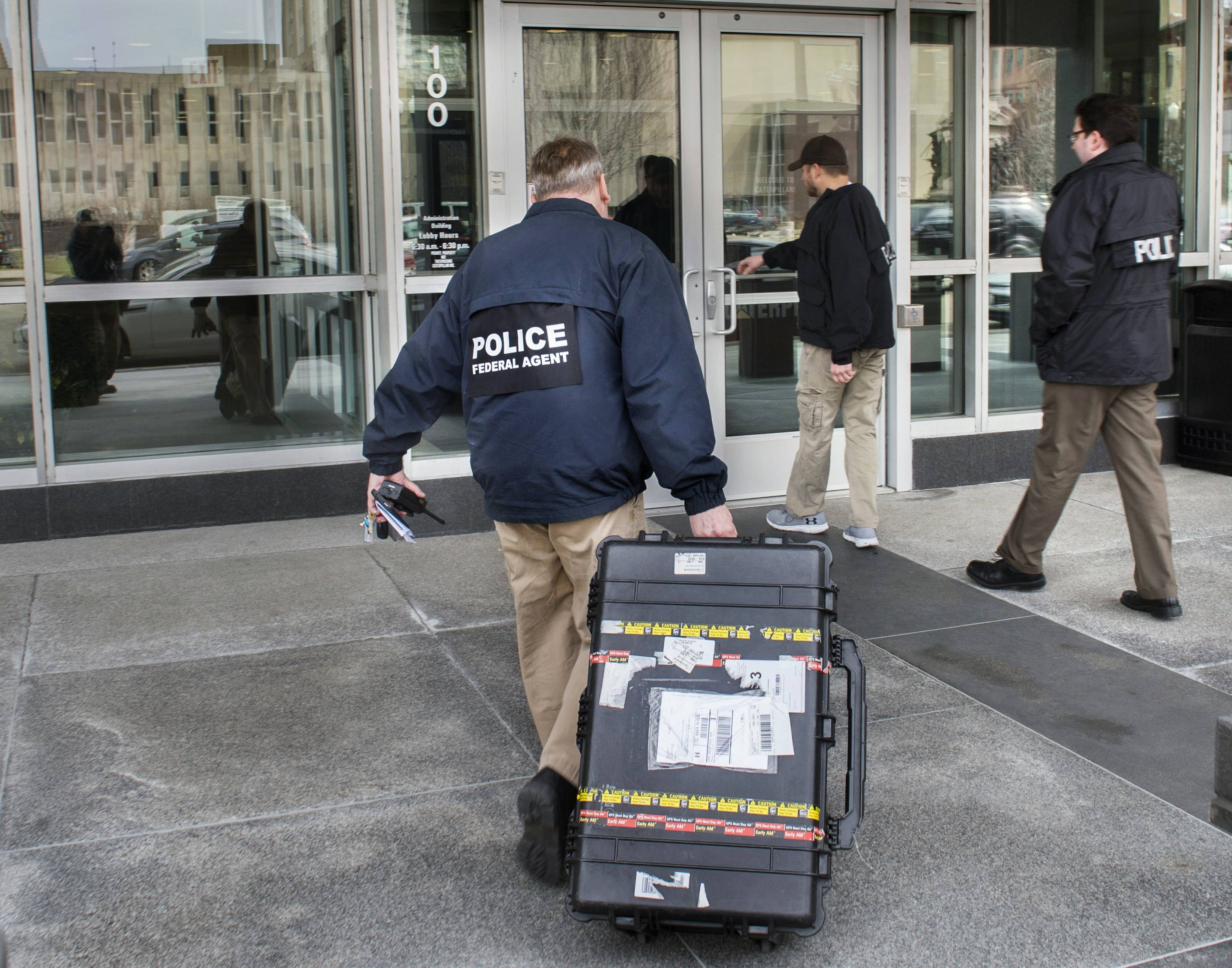 Federal law enforcement agents enter the headquarters of Caterpillar Inc. in Peoria on Thursday after a search warrant was executed at three downstate Caterpillar facilities: Peoria, East Peoria and Morton.