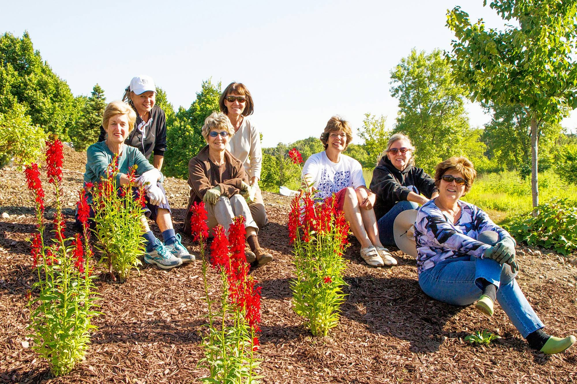 Members of the South Barrington Garden Club rest after planting native species in the South Barrington Conservancy, a 35-acre plot of land set aside for the preservation and restoration of wooded and wetland prairies.