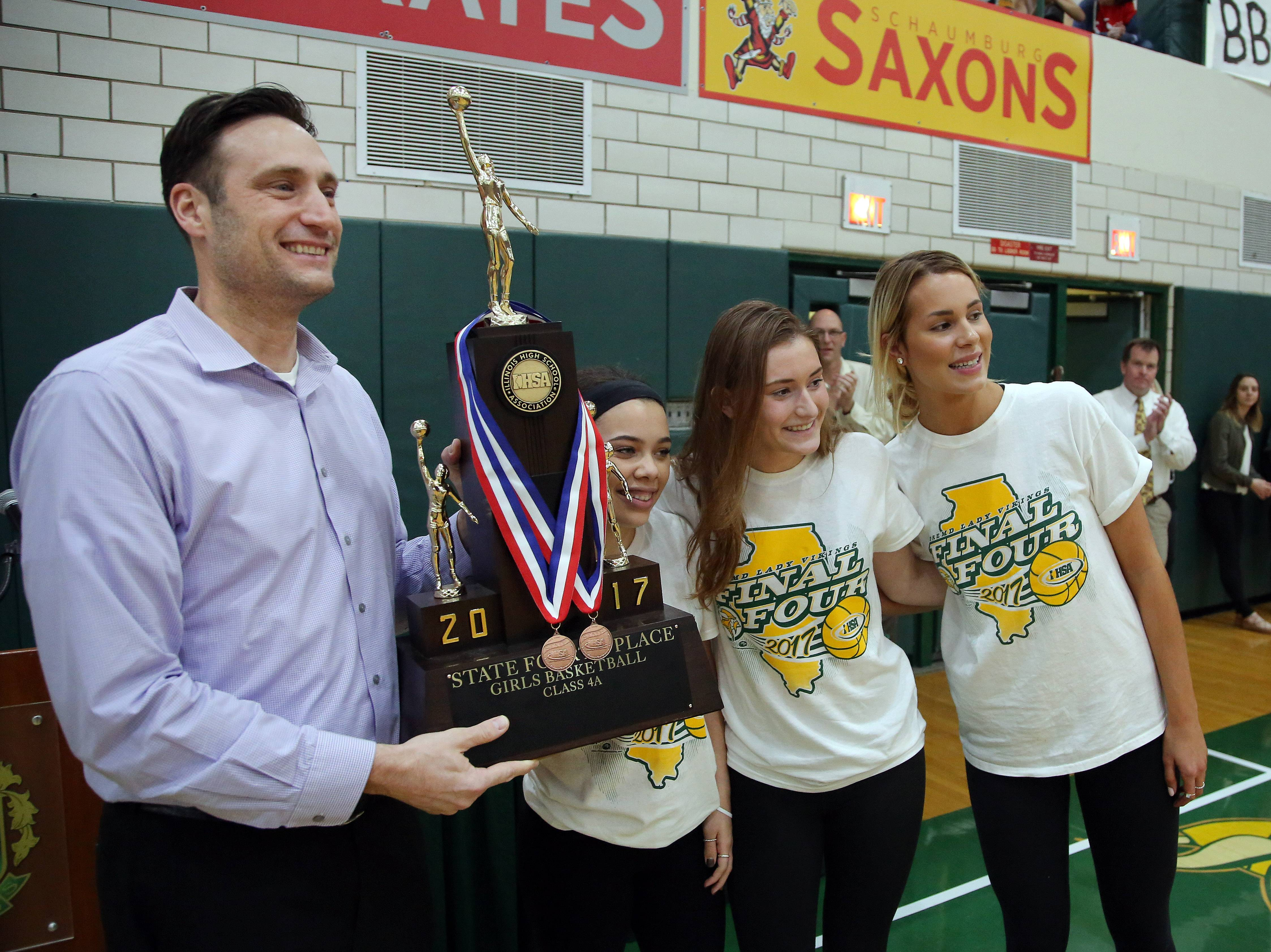 Fremd High School Principal Kurt Tenopir, left, is presented with the fourth-place Class 4A girls basketball trophy by team captains Hayley Williams, Missy Adrian and Grace Tworek during a school assembly Monday in Palatine.