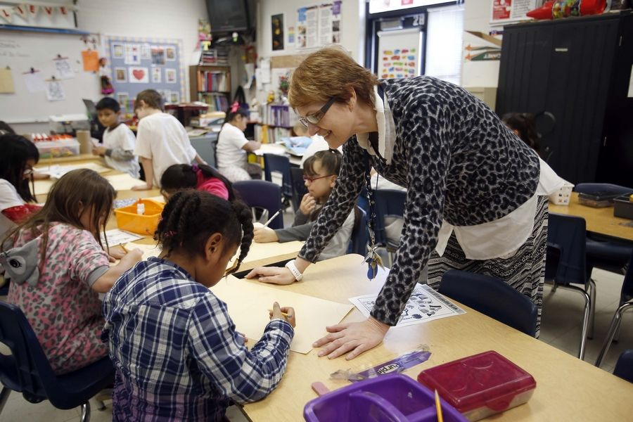 Art teacher Cindy Walker works with students Thursday at Hillcrest Elementary School in Elgin. Music and visual arts currently are offered once a week for 40 minutes in first- through sixth-grade classrooms.