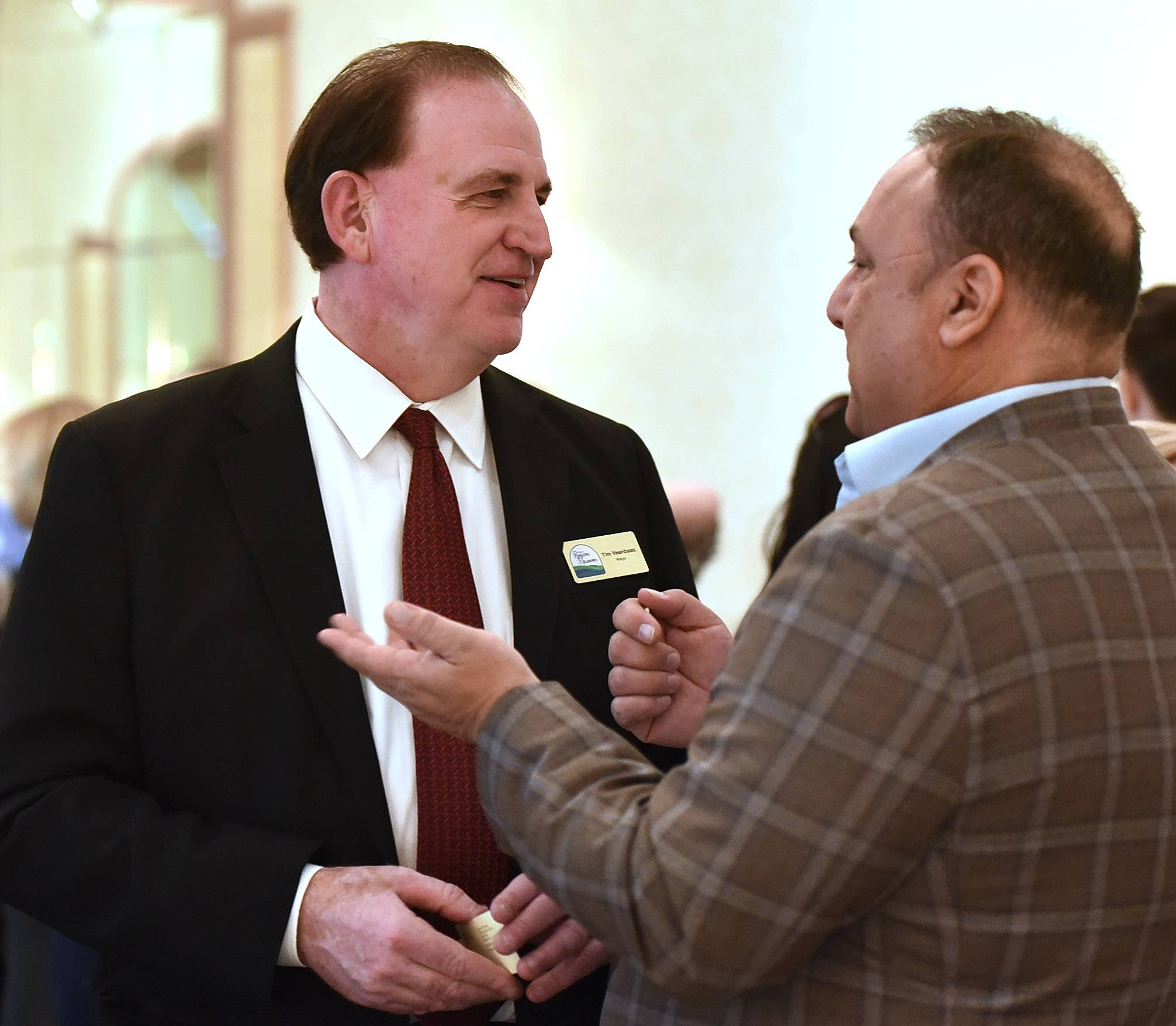 Rolling Meadows acting Mayor Tim Veenbaas talks with David O. Stein of Deer Park Investors at the chamber's 12th annual Taking Care of Business luncheon on Wednesday.