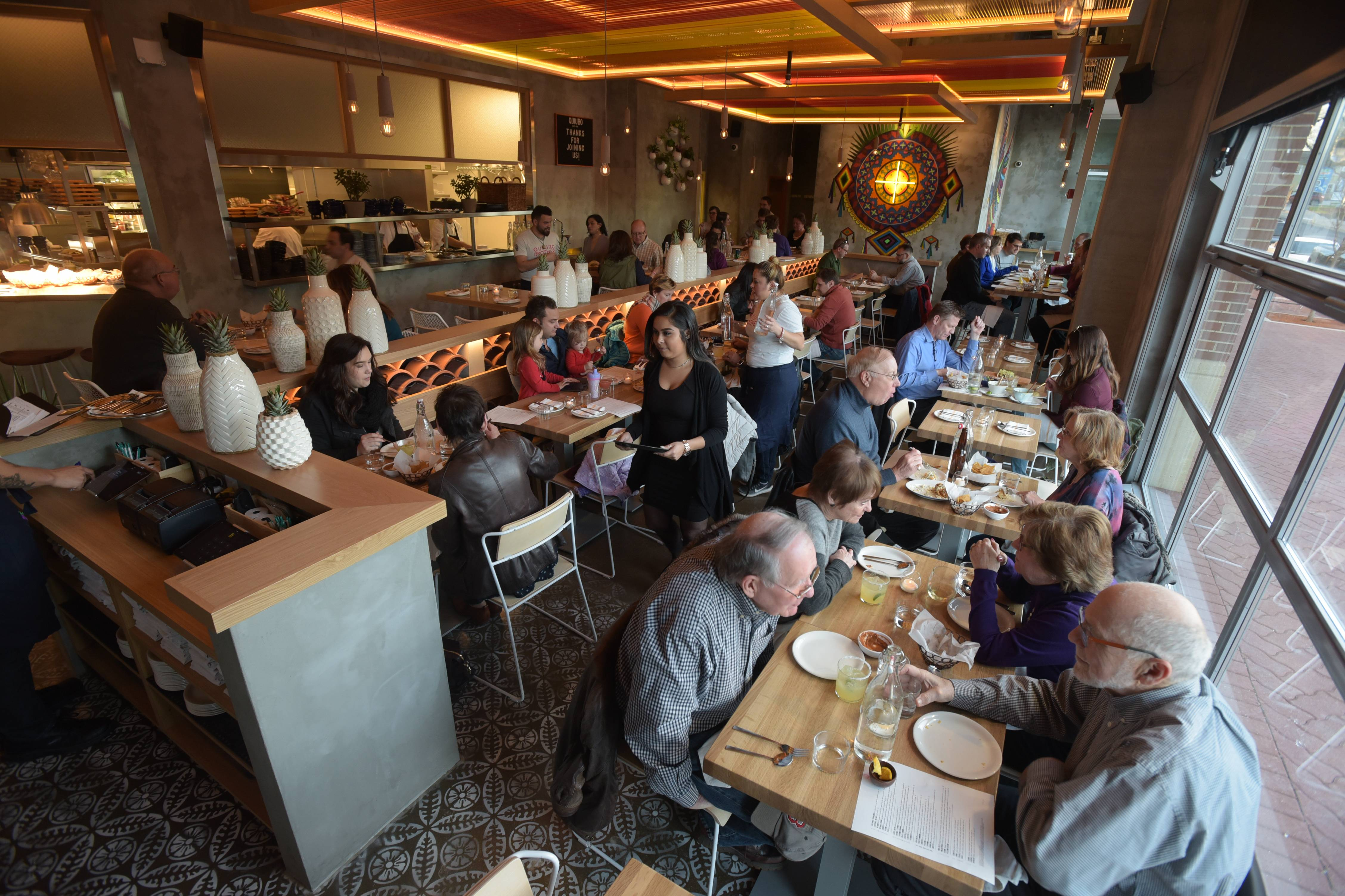 Patrons fill Quiubo on Wednesday evening as the new Mexican restaurant hosts its opening night in the Water Street District in downtown Naperville.