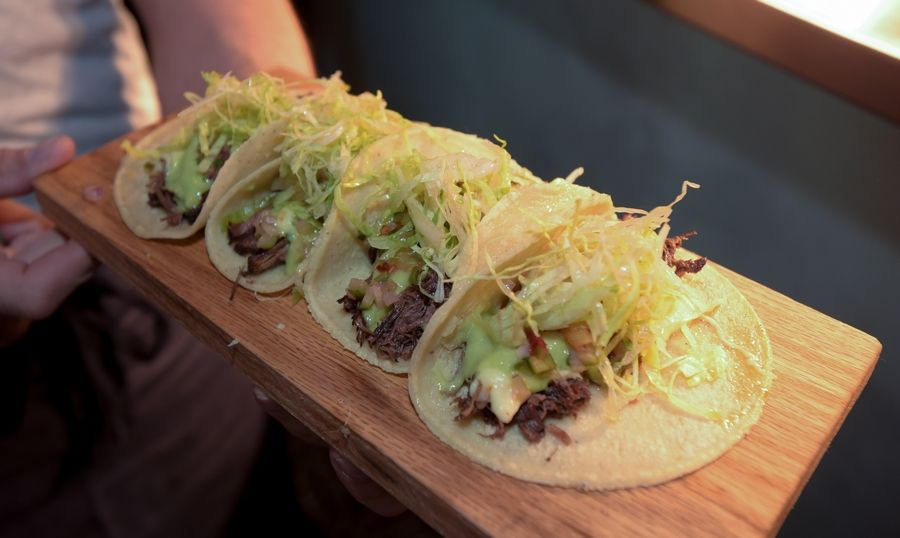 "A server brings out a board of tacos Wednesday from the kitchen of Quiubo, a restaurant named for the Mexican slang word for ""what's up?"" that opened this week in the Water Street District in downtown Naperville."