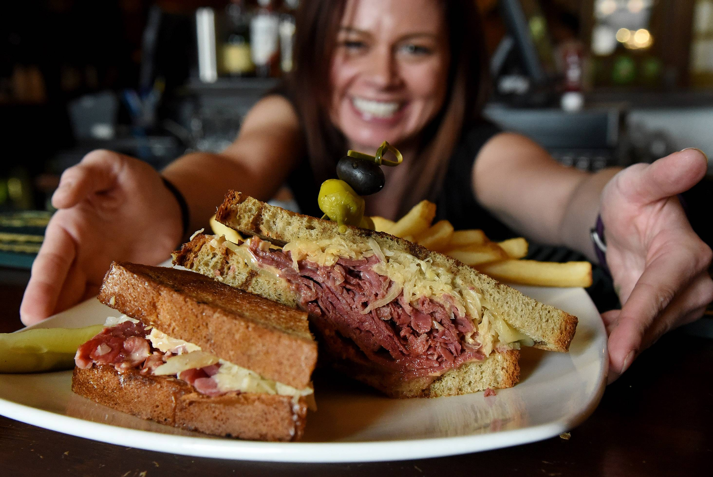 Bartender and manager Chrissy Barnard serves up a traditional corned beef on rye sandwich with sauerkraut at McGonigal's Pub in Barrington.