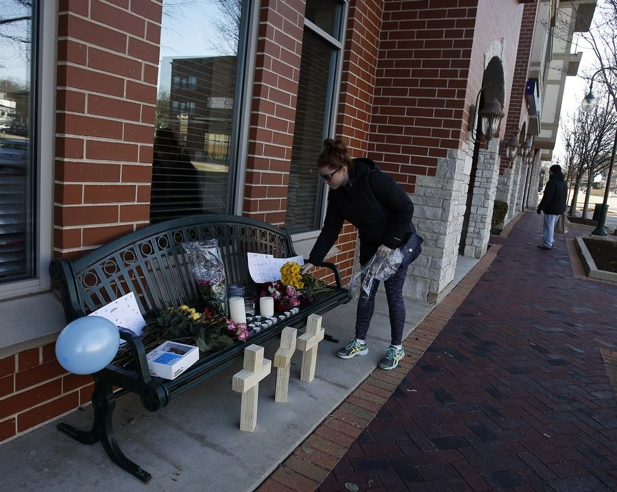 An woman places flowers at a memorial outside the scene where four people were shot Friday in St. Charles, police say.